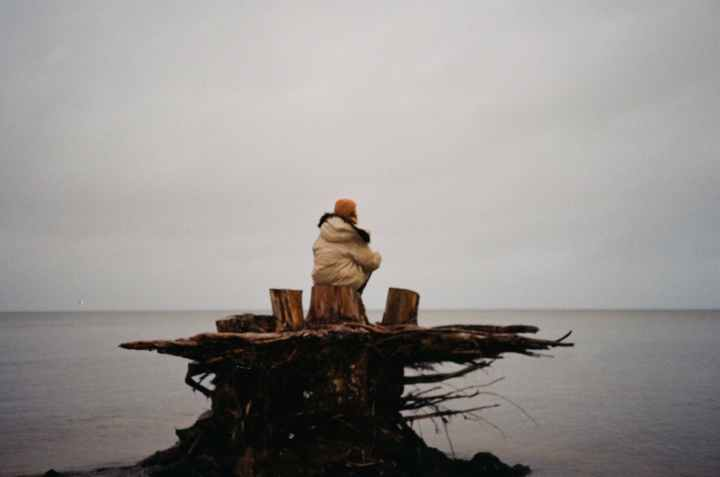 photo of person sitting on tree stump near body of water